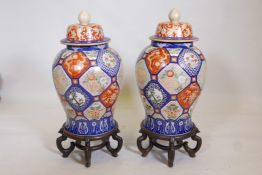 A pair of Oriental ceramic jars and covers, decorated with bright enamels in the Imari style, with