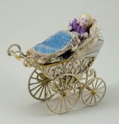 Miniature painted soft metal pram and doll, German circa 1890,