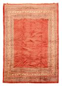 Araak red ground rug, field decorated with repeating Boteh motifs, graduated multicoloured striped g