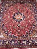 Kashan red ground rug carpet, the field decorated with scrolling stylised foliage with central medal