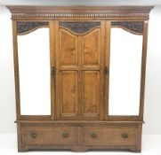 Early 20th century carved oak triple wardrobe, with two shaped mirrored doors, two drawers to base w
