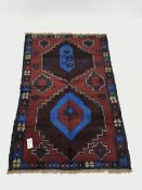 Baluchi red and blue ground rug, two medallions, 130cm x 83cm
