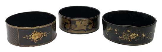 Two Regency black papier-maché wine coasters, together with a toleware example, each with gilt folia