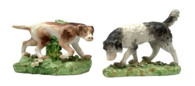 Two 19th century Staffordshire models of hunting dogs, each stood upon naturalistically modelled bas