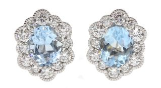 Pair of 18ct white gold oval aquamarine and diamond cluster stud earrings, hallmarked, total aquamar