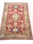 Turkish style red ground rug, repeating border, central medallion, 250cm x 160cm