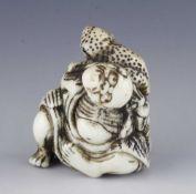 An ivory netsuke of an oni with frog