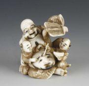 An ivory netsuke Hotoi with his children