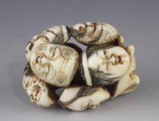 An ivory netsuke of 9 Noh masks