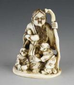 An ivory netsuke of 3 figures