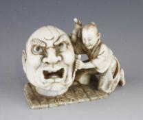 """A 2"""" ivory okimono of a mask maker"""