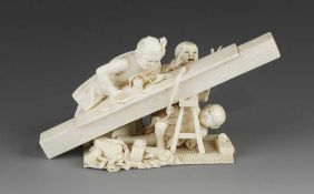 """An ivory okimono of a carpenter planing timber with his children getting under his feet 6"""" x 3"""""""