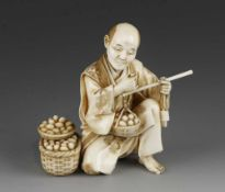 """A 4"""" ivory okimono of a man weighing eggs signed"""