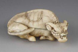 """A 2 1/2"""" ivory okimono of a recumbent ox"""