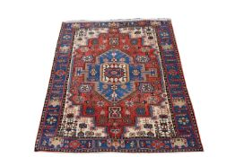 A Hamadan rug, North West Persian, the madder field with a central polychrome medallion, ivory