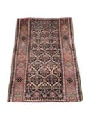 A Kurdish rug, the charcoal compartment field filled with stylised plants, within a madder