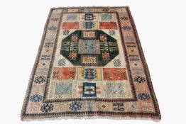A Turkish carpet, the ivory field with a central green octagonal medallion with hooked guls.