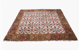 An Indian carpet, the ivory field with all over trellis design enclosing palmettes, within a
