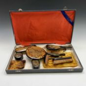 A Chinese faux tortoiseshell dressing table set, early 20th century, gilt decorated with stylised