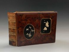 A Japanese red lacquer photo album, late 19th century, the cover with floral sprays and two panels