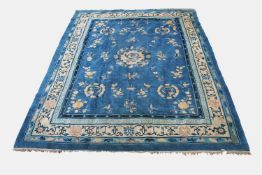 A Chinese Peking carpet, the indigo field with a central circular medallion enclosing a dragon,