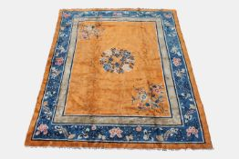 A Chinese Peking carpet, the apricot field with a central circular floral medallion and opposing