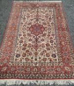 An Esfahan carpet, West Persia, the ivory field with a madder floral medallion, scrolling vines,