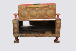 An Indian low table, the lift up front with circular brass mounts, surmounted by four turned