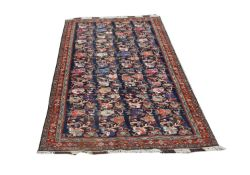 A North West Persian carpet, the indigo field with rows of polychrome flowering branches, within a