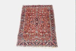 A Heriz rug, North West Persia, the madder field with a central polychrome lobed medallion,