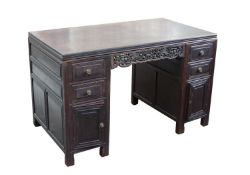 A Chinese hardwood twin pedestal desk, late 19th century, with bat and roundel carved stretchers,