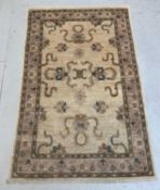 A Ziegler Chobi rug, the ivory field with palmettes and flowering vines, within a meandering