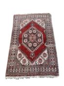 A South West Persian rug, the madder field with a charcoal hooked lozenge medallion, with