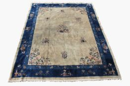 A Chinese Peking carpet, circa 1900, the camel/beige field with a central flowering tree and vases