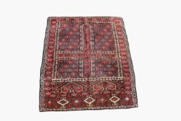 A Turkoman Hatchli rug, the quartered field with central mihrab and serrated guls, within a madder