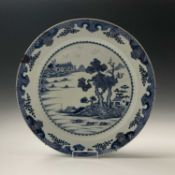 A large Chinese blue and white porcelain charger, 18th century, depicting a riverside scene,