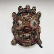 A Bhutanese ceremonial painted carved wood mask, 35 x 29cm.
