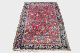 A Heriz carpet, North West Persia, the madder field with an all over design of palmettes , flowering