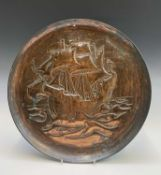 An Arts and Crafts period copper charger, repousse decorated with a galleon, unmarked. Diameter 36.