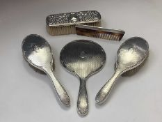 A pair of silver-mounted brushes, a matching mirror and an ornate silver-mounted brush and a