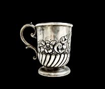 An Edwardian silver christening mug, half spiral fluted and embossed with flowers and scrolls.
