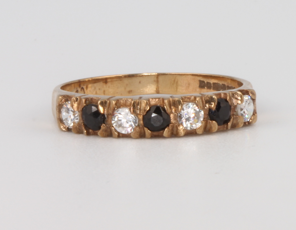 Lot 592 - A 9ct yellow gold gem set half eternity ring size M, 1.9 grams