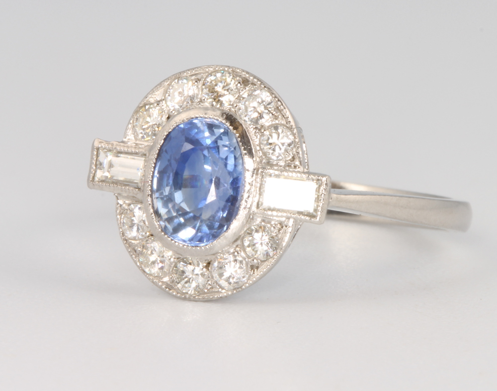 Lot 563 - A platinum oval sapphire and diamond cluster ring, the centre stone approx. 1.2ct, the baguette