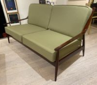 A DANISH SETTEE, 1970's WITH RAILED BACK , SHAPED ARMS ON TAPERING LEGS.