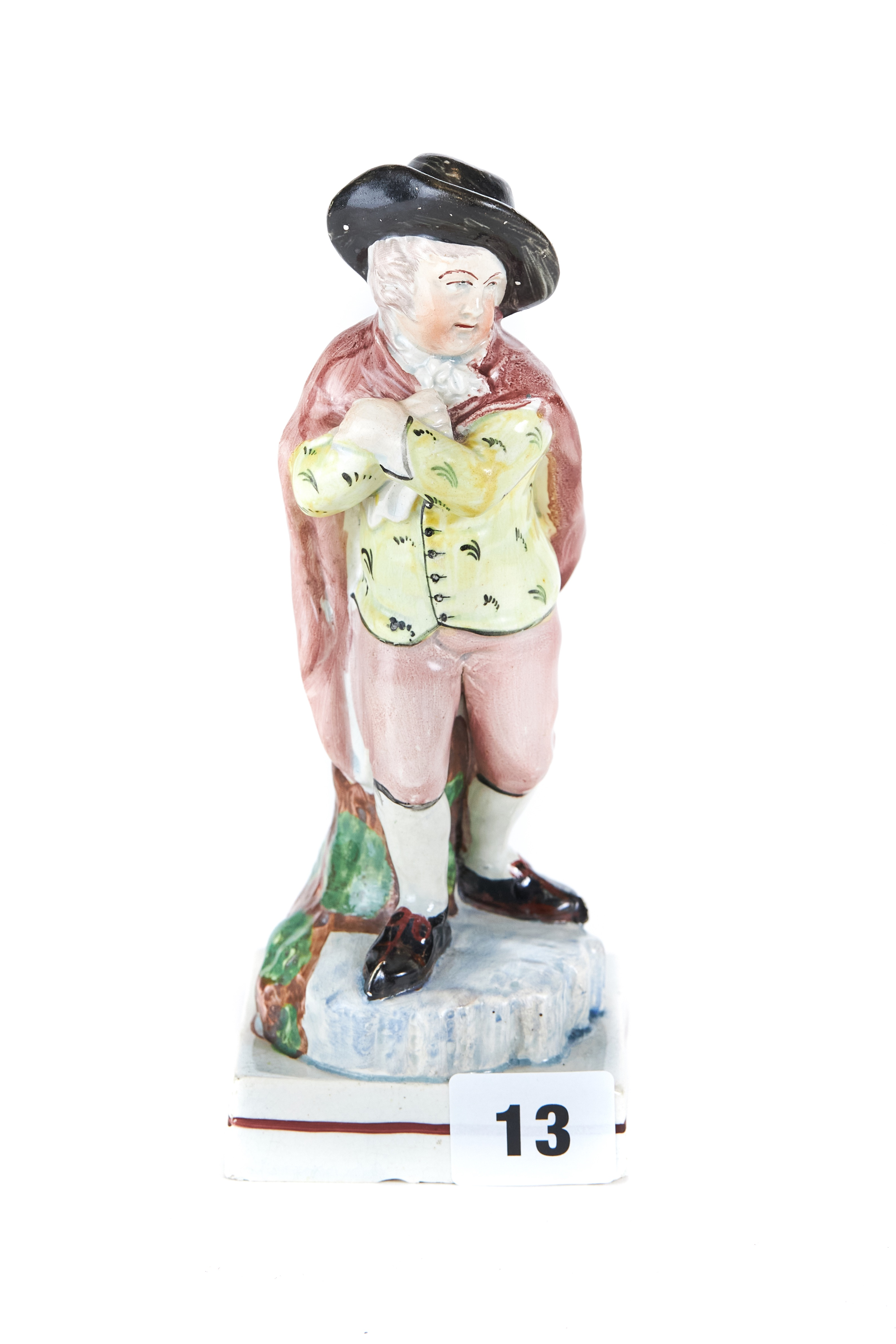 Lot 13 - AN 18TH CENTURY ENGLISH POTTERY WOOD TYPE FIGURE of a male ice skater wearing a brown cloak,