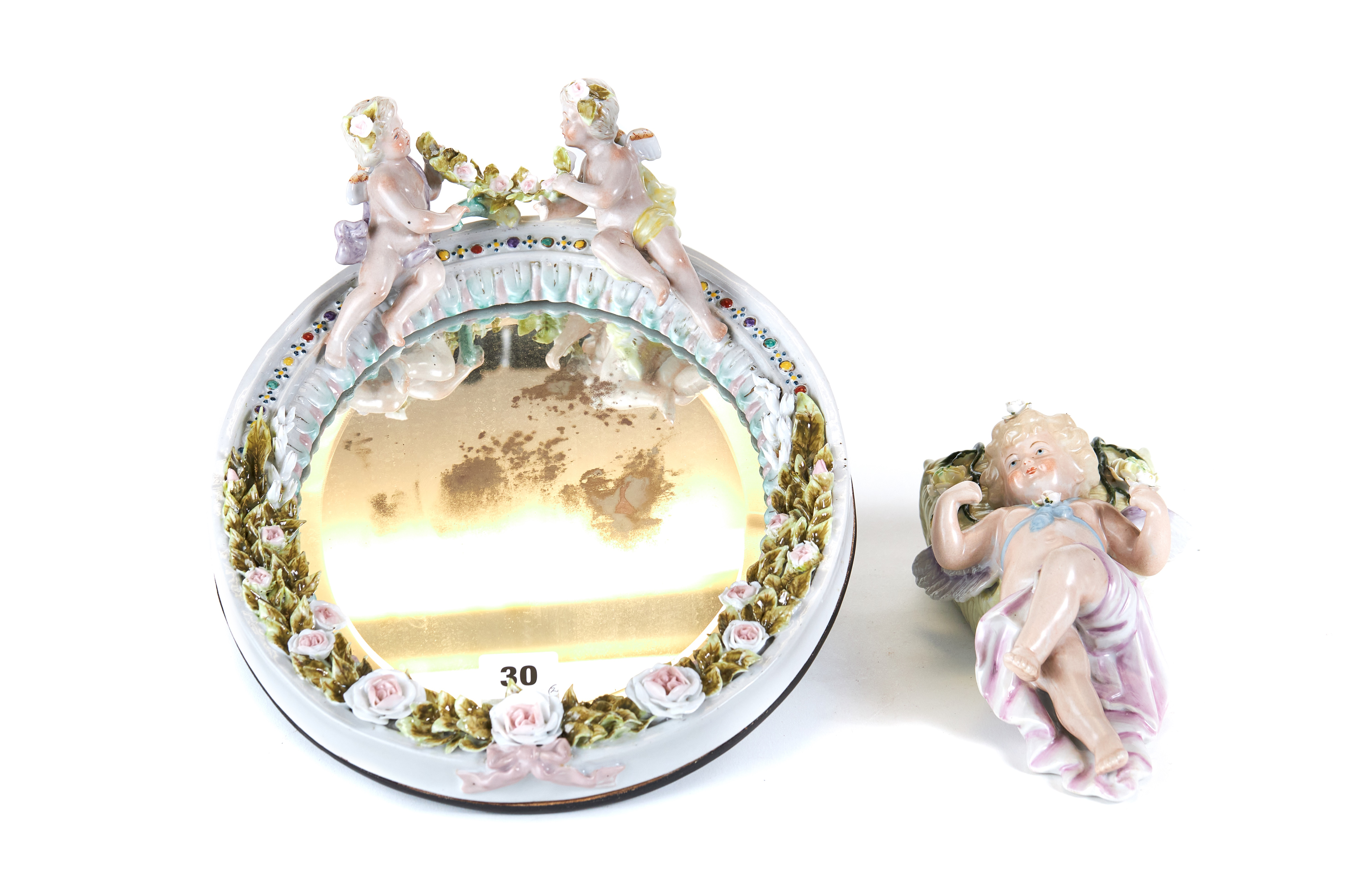 Lot 30 - A LATE 19TH CENTURY OVAL CONTINENTAL PORCELAIN WALL MIRROR the flower encrusted frame surmounted by
