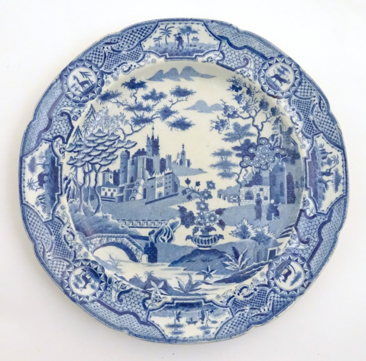 Lot 37 - A Spode blue and white plate decorated with a stylised landscape, with trees, flowers, bridges,