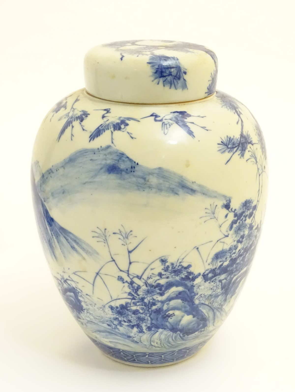 Lot 21 - A large blue and white Japanese lidded ginger jar decorated with a sage sat by a tree in a