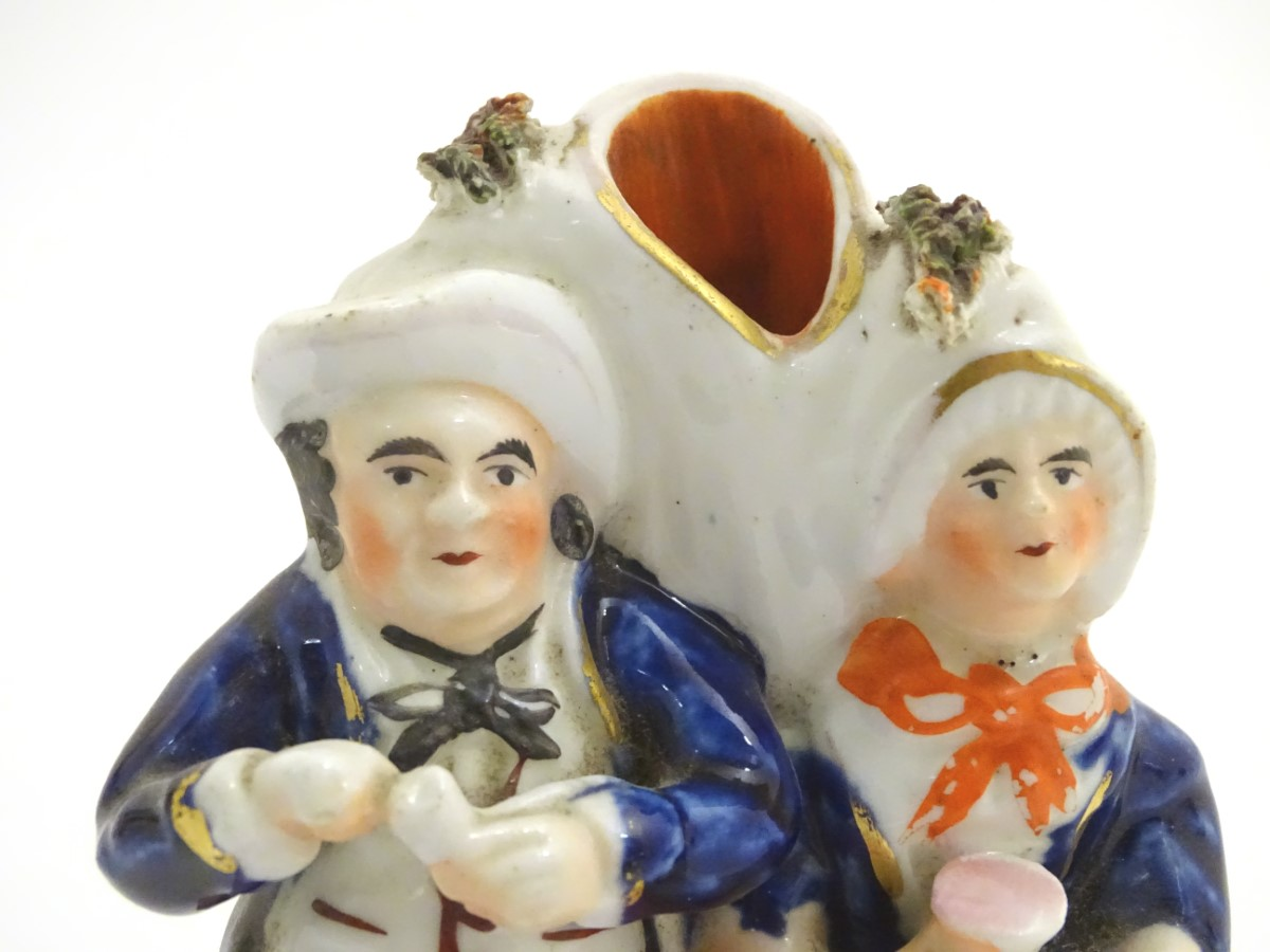 Lot 41 - A Victorian Staffordshire pottery flatback spill vase depicting a man and a woman,