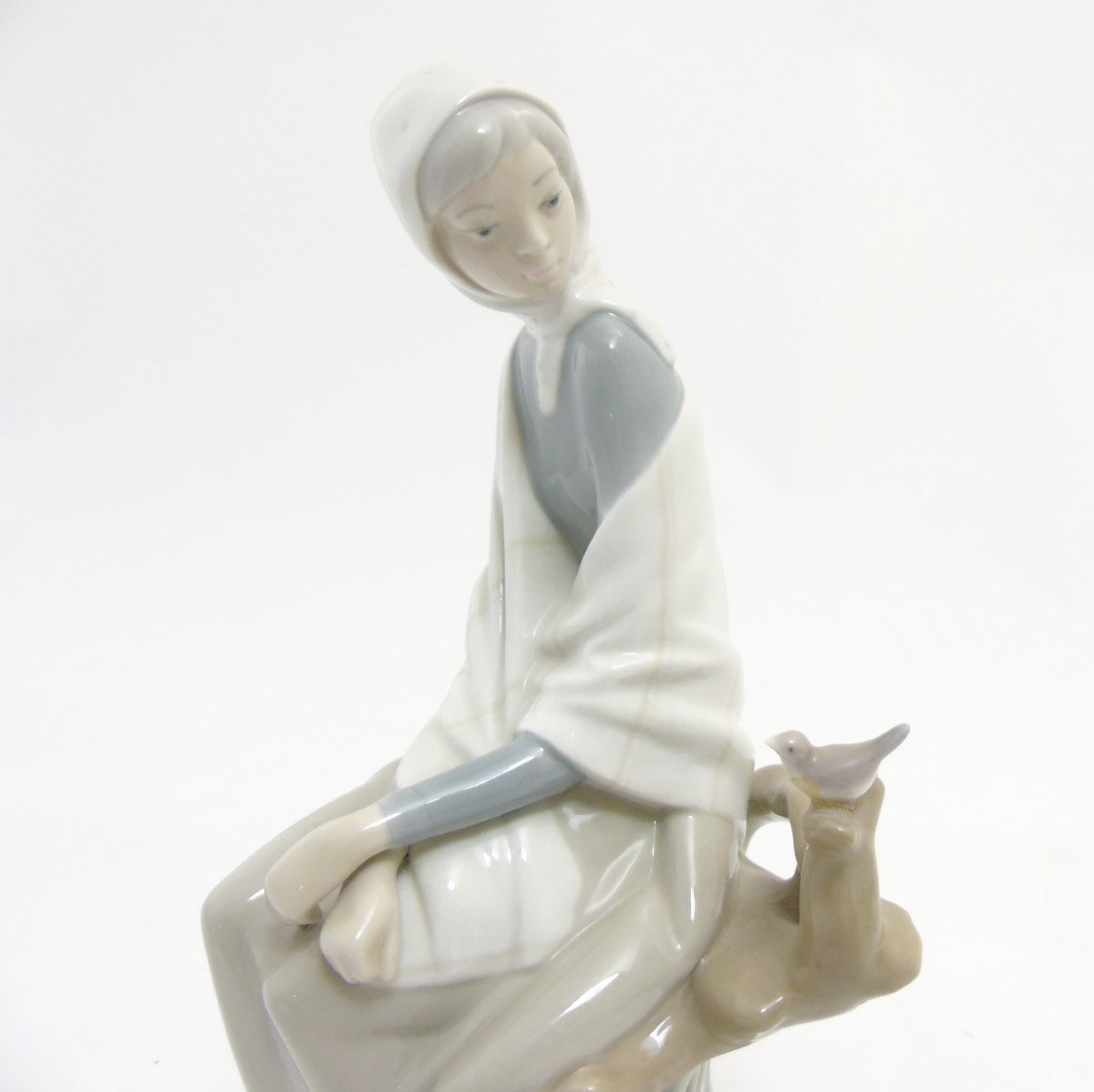 Lot 47 - A Lladro 'New Shepherdess' figurine of a girl sat watching a bird, makers mark to base,